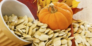 Toasted pumpkin seeds spilling from a yellow bowl